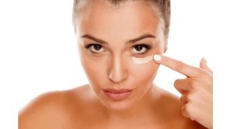 Eine natürliche Frau schminkt sich unter dem Auge mit Concealer.