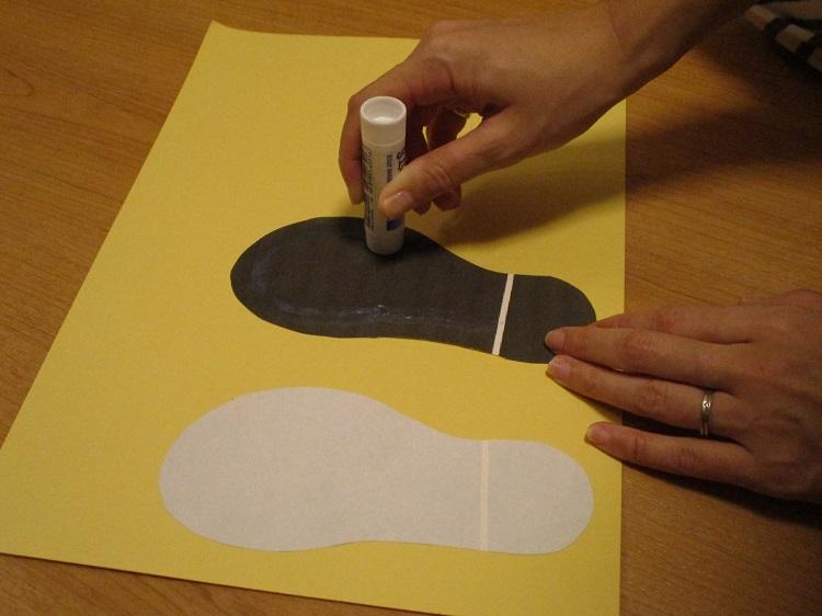 子供が靴を揃える足形にのりを塗る