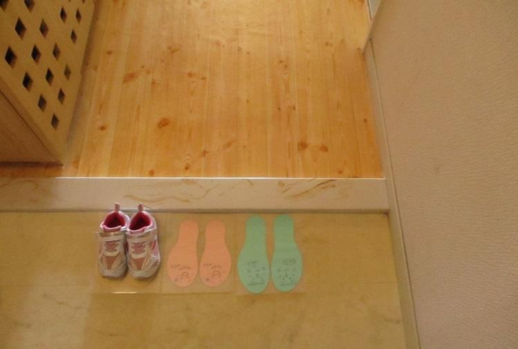 子供が靴を揃える足形玄関