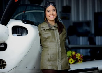 Jessica Cox in front of an airplane, in a nicely tailored jacket.