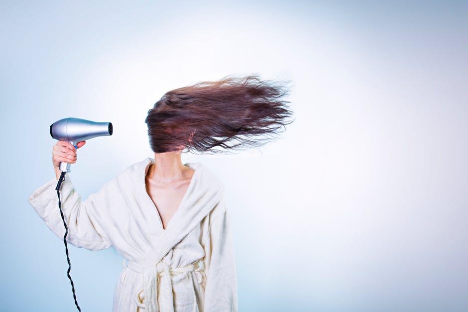 Woman wearing bathrobe and drying her hair