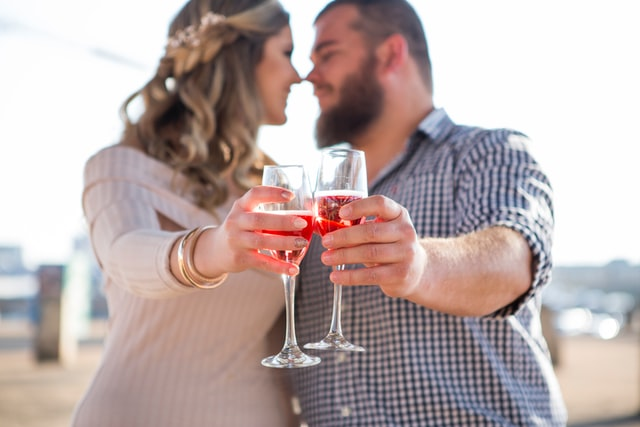 Man and Woman looking into each others eyes with wine glasses