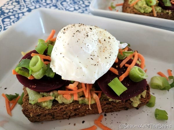 Beet and avocadoes on a toasted bread with a poached egg and pepper on top.