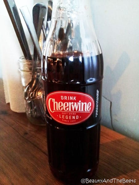 bottle of cheerwine and silverware behind the bottle