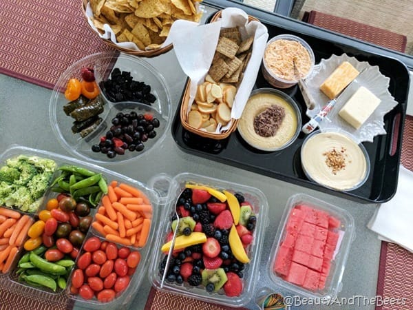 a spread of vegetables, fruit, olives, cheese and crackers on red placemats