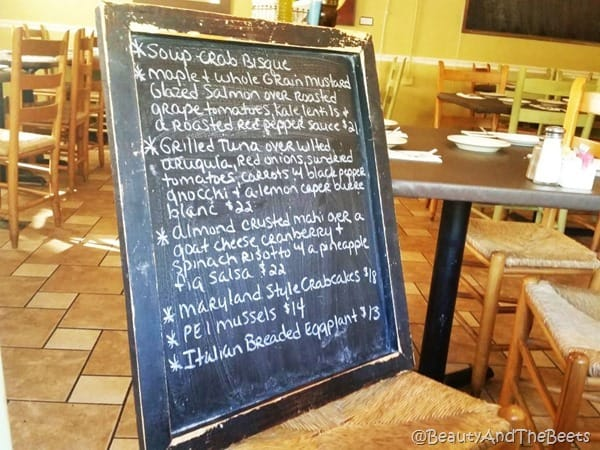 A blackboardd sitting on a table with a listing of the dinner specials