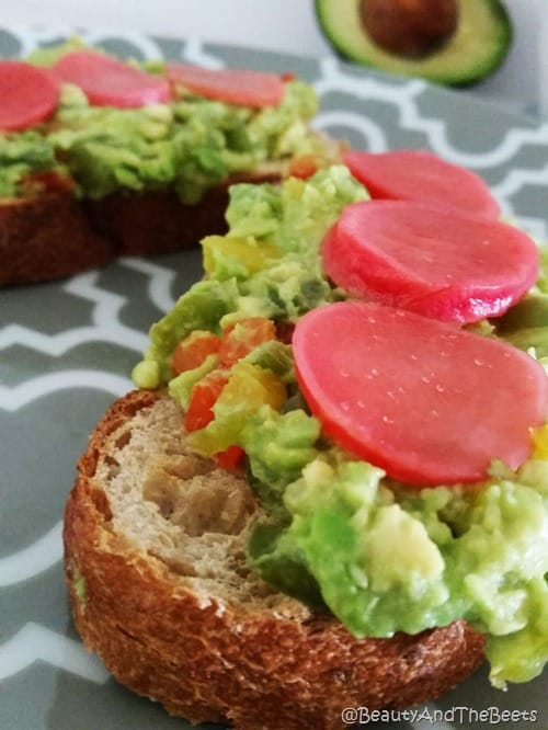 Toast topped with mashed avocado and bright pink pickled beets on a gray plate