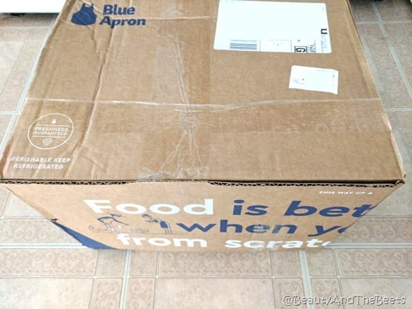a large cardboard box from Blue Apron on a kitchen floor