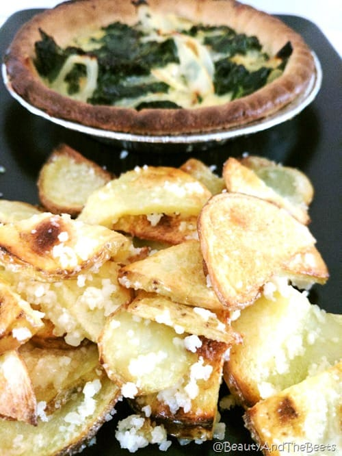 a pile of potatoes and garlic chips with an egg and kale pie tart in the bakcground on a black plate