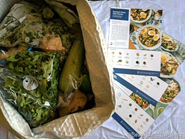 A box of bagged ingredients alongside of a grouping of recipe cards