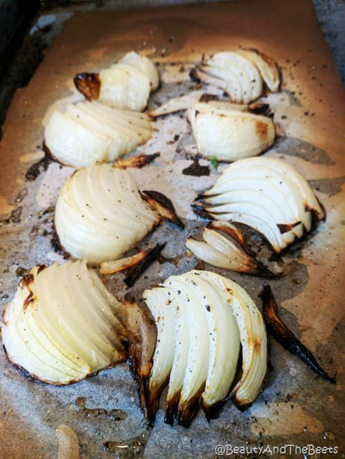 a baking sheet with roasted onion wedges on parchment paper