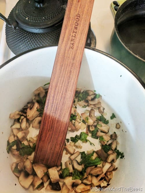 a white stock pot with sauteed mushrooms and mustard greens with a wooden Earlywood spatula with a black cast iron tea pot in the background on a white stove