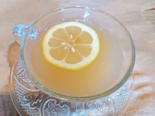 a crystal punch cup filled with yellow boozy punch and a floating lemon slice on a doilied glass punch plate against a light brown background