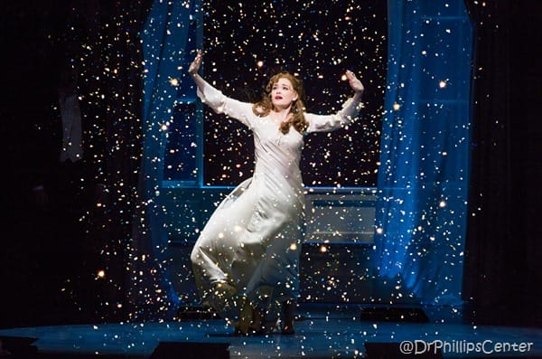 The character of Slyvia on stage mid song with a sprinkling of sparkly pixie dust