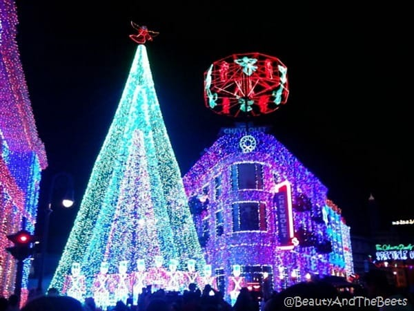 bright green lighted Christmas tree and a bright purple decorated lighted building