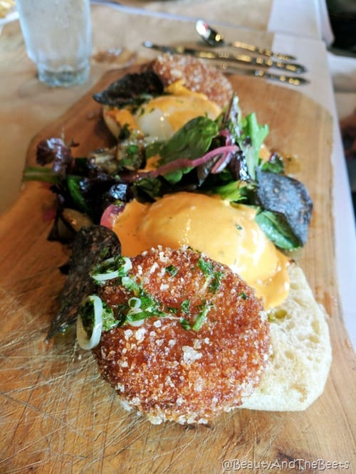 an english muffin with a golden brown round crabcake topped with a poached egg and spicy hollandaise sauce and dressed greens on a wooden cutting board