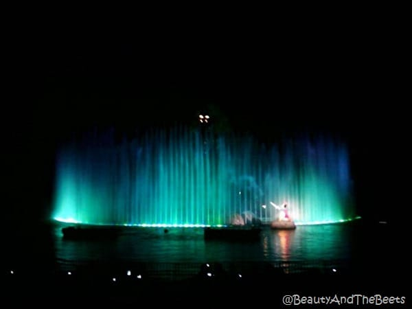 streams of green lights on a water fountain with Mickey Mouse lit up in the front