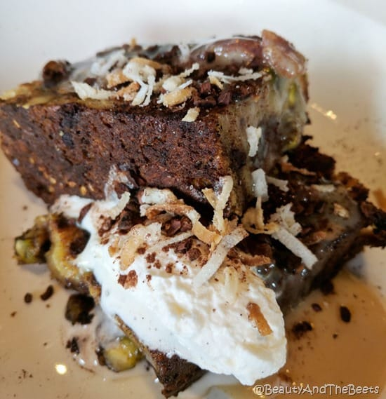 two slices of chocolae bread pudding angled on a white plate with whipped cream and shredded toasted coconut and pistachio shavings