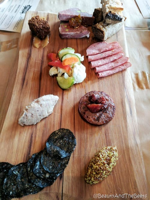 a wooden board with various meats, pork pate, vegetables on a wooden cutting board on a wooden table
