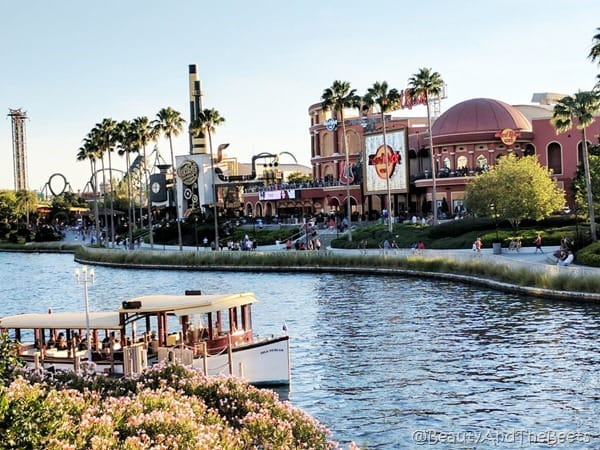 The Hard Rock Cafe Orlando in the background behind a small river with boats