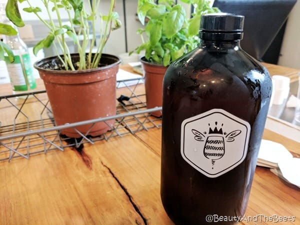 a single growler with bee logo in front of a pair of small potted plants