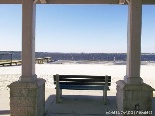 a park bench under an awning on the beach at Lake Minneola with a dock in the background