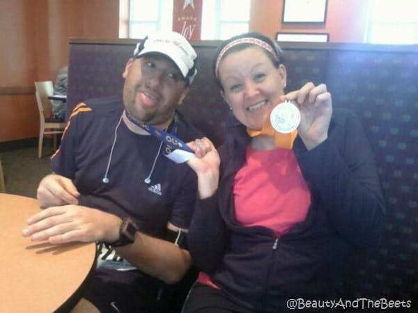 the author showing off her medal in a booth at Panera while brother looks on