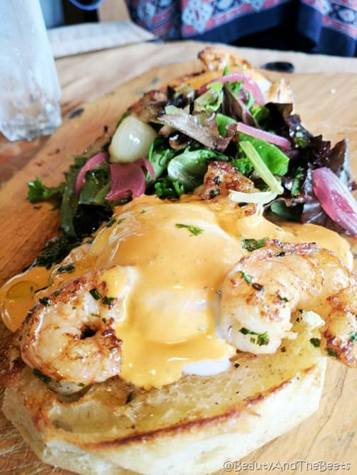an english muffin topped with poached egg, grilled shrimp and a spicy hollandaise on a wooden plate with a pile of dressed greens