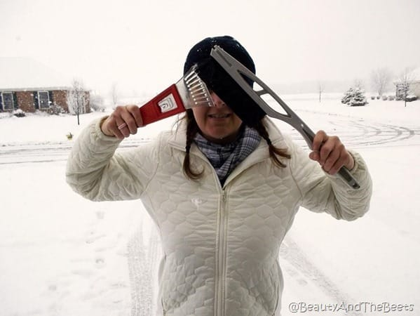 the author wearing a white jacket and black knit cap with snow removal brush and scraper covering her eyes with a snowy background