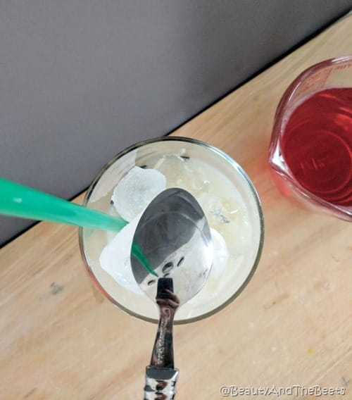 a glass with a green straw and ice with the backside of a spoon over top next to a glass of red tea