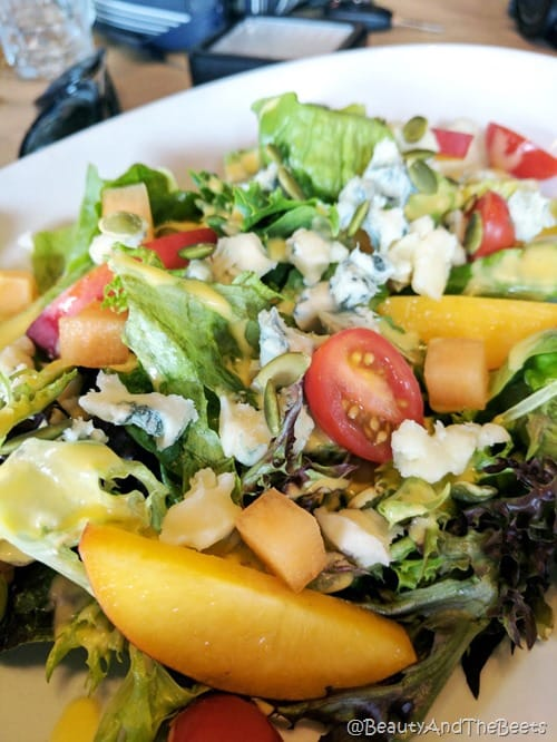 a salad with cherry tomatoes, mangoes, pineapple, blue cheese on a white plate