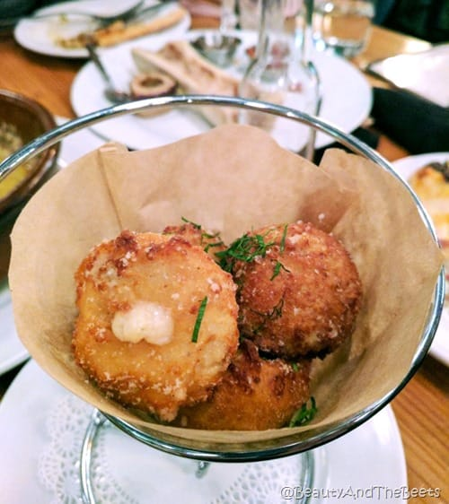 A wire basket with round fried balls of cheese with a background of other dishes on a table