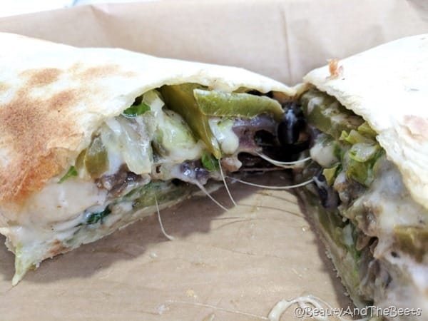 a quesadilla halved stuffed with oozing cheese, green peppers and onions on a paper plate