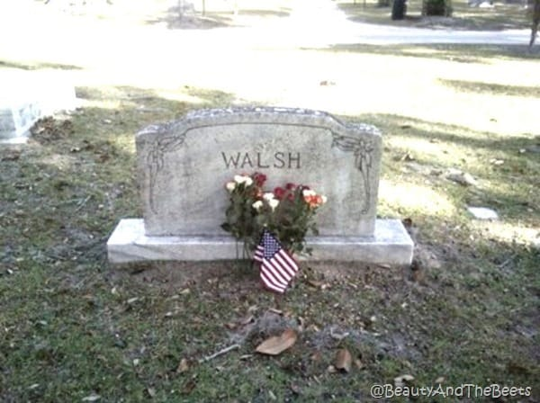 a granite headstone with the Walsh name with an AMerican flag and a bouquet of flowers in front of it