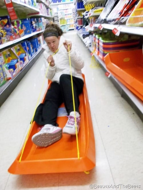 the author testing an orange sled in the middle of an aisle in a shopping market