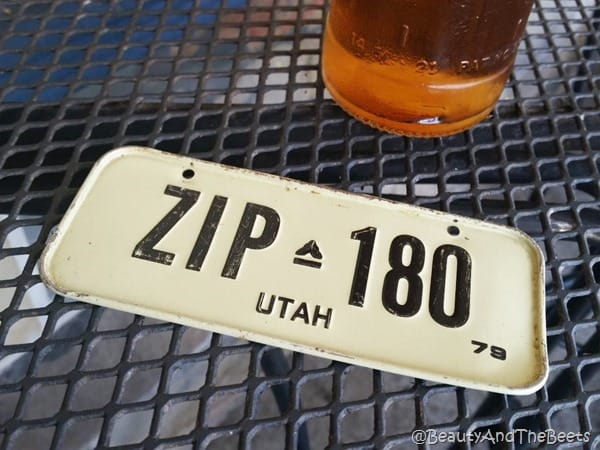 a white license plate with black lettering on a black mesh table