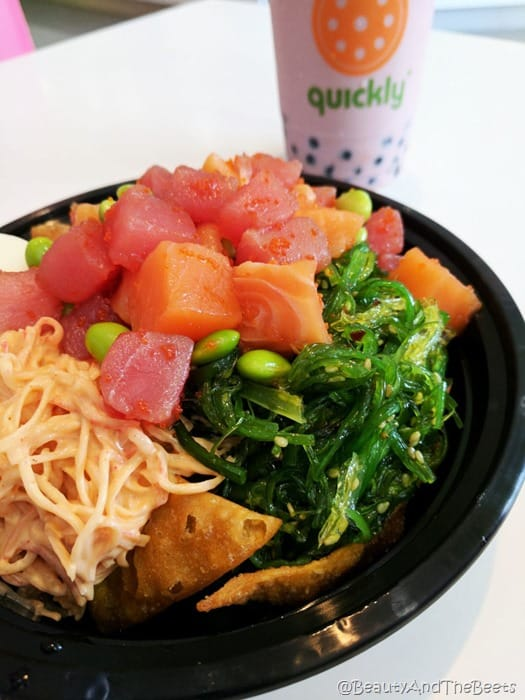a poke bowl with tuna, salmon, krab salad, edamame, seaweed salad and wontons in a black bowl on a white table with a cup of blueberry boba milk tea in the background