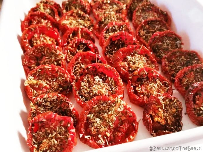4 rows of sliced slow roasted wrinkled tomatoes filled with herbs and seasonings in a white casserole dish