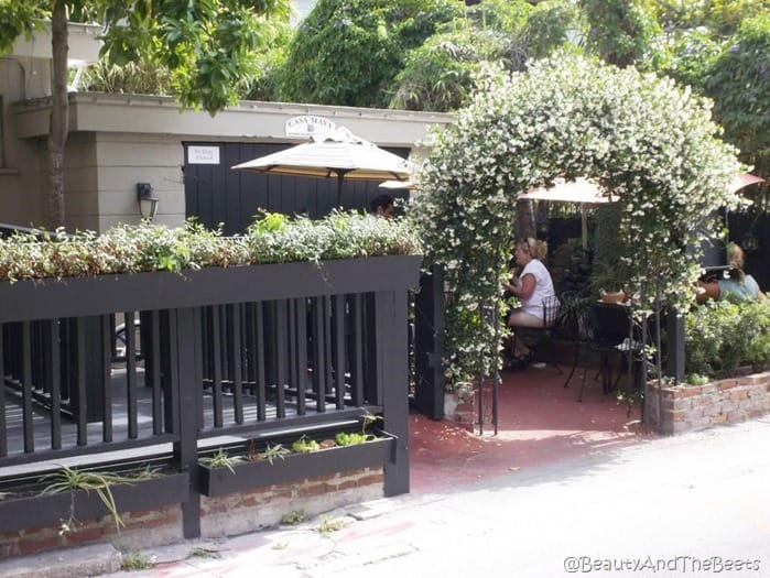 a garden courtyard patio with a wrought iron railing and restaurant tables under a green plant arch