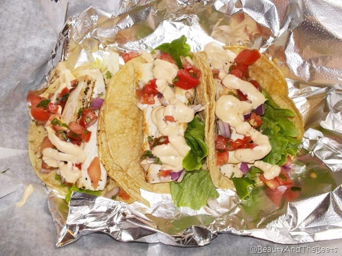 a trio of flour tortillas topped with griiled fish, lettuce and tomatoes with a mayo sauce on aluminum foil