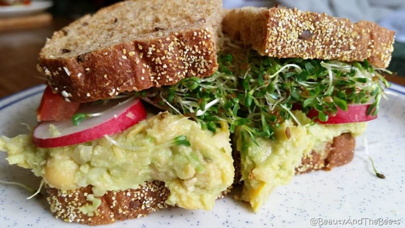 whole grain bread in a sandwhich with chickpea mash spread, radishes and sprouts on a white plate