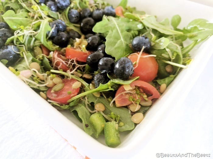 a square dish with arugula, red tomatoes, and ripe blueberries on a white plate with white background