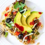 whole30 taco casserole on a plate with avocado and hot sauce