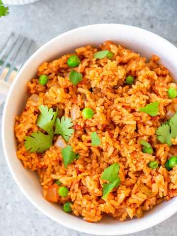 prepared Spanish rice in a bowl with cilantro garnish