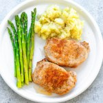 pork cops on a plate with mashed potatoes and asparagus