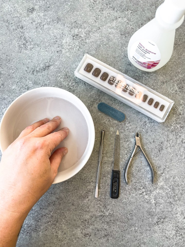 soaking cuticles in warm water in a small white bowl