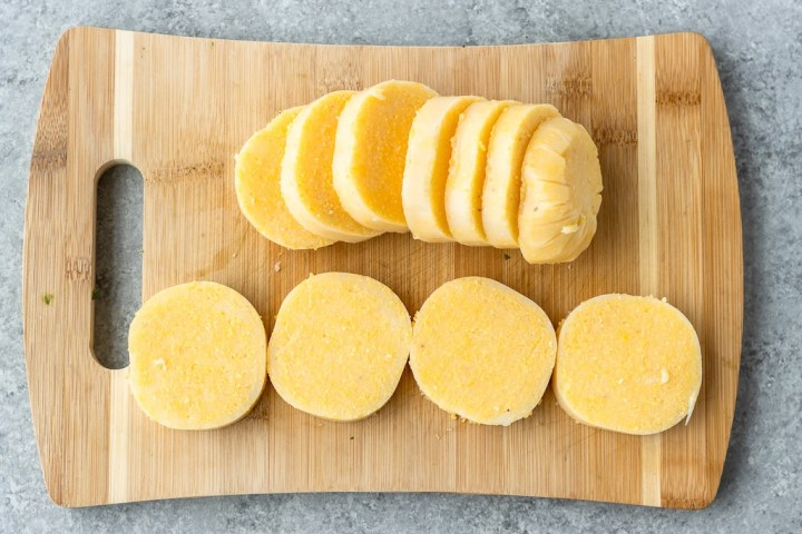 tubed polenta sliced into rounds on a cutting board