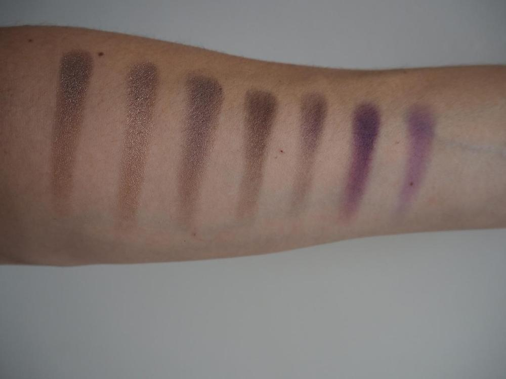 Row of eyeshadow swatches on my arm from Morphe 35d palette ambers and purple