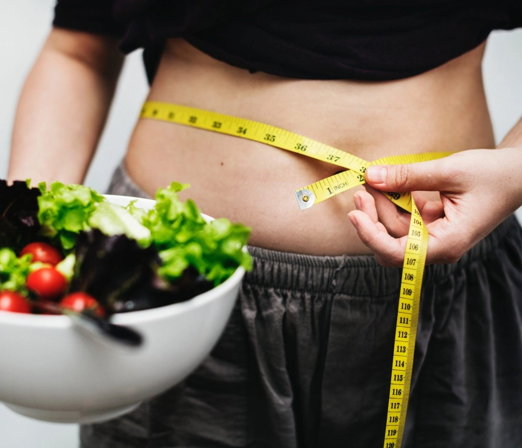 Person measure waistline with a measuring tape while holding a salad