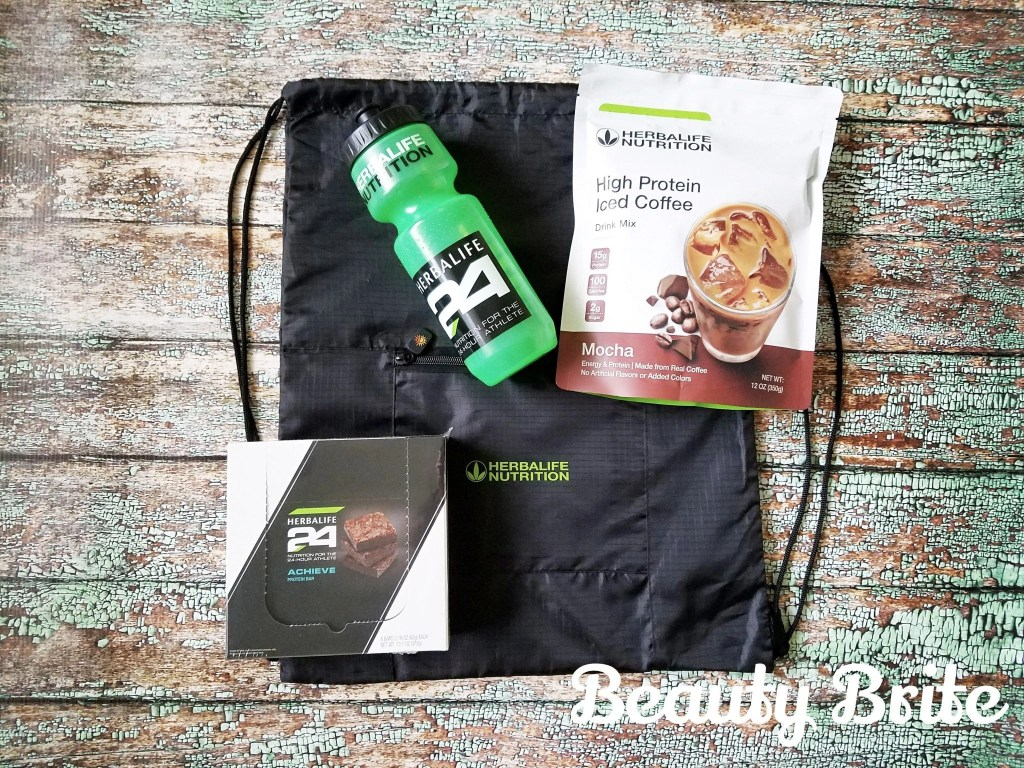 Herbalife High Protein Iced Coffee, nylon bag, water bottle, and a box of Achieve Bars